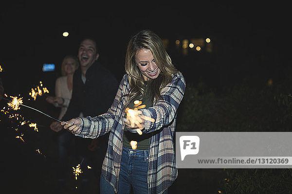 Freunde spielen nachts mit Wunderkerzen