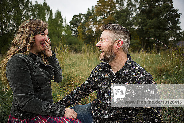 Happy couple looking at each other while sitting on grassy field in farm