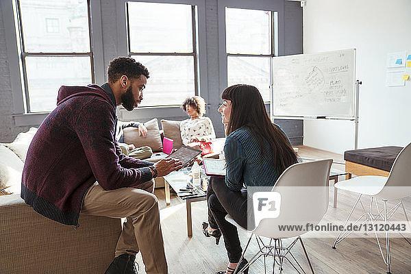 Geschäftsleute  die sich unterhalten  während sie im Büro sitzen