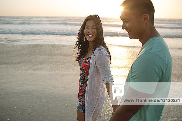 Happy couple walking on shore at beach during sunset