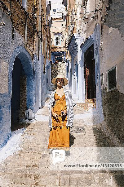 Portrait of woman walking in alley amidst old buildings