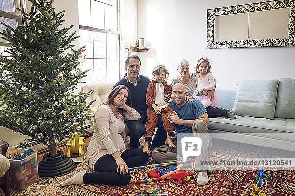 Porträt einer lächelnden Familie am Weihnachtsbaum zu Hause