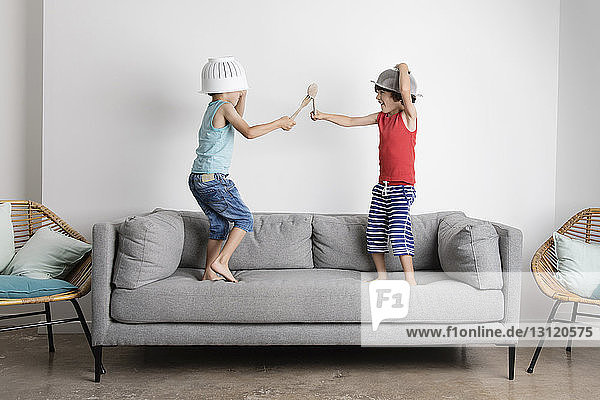 Happy brothers fighting with wooden spoons while standing on sofa against wall at home
