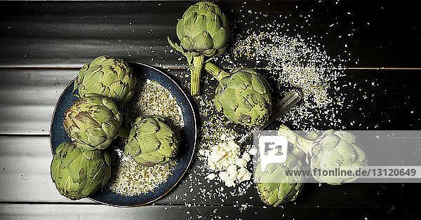 Overhead view of artichokes with cheese on table