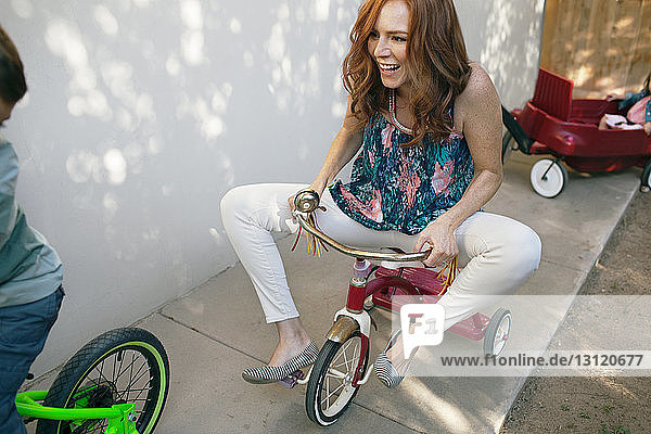 Playful mother riding tricycle with boy at backyard