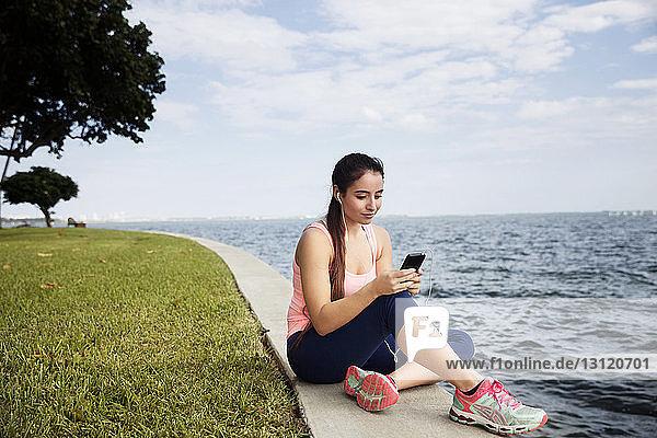 Junge Frau benutzt Smartphone,  während sie am Meer gegen den Himmel sitzt
