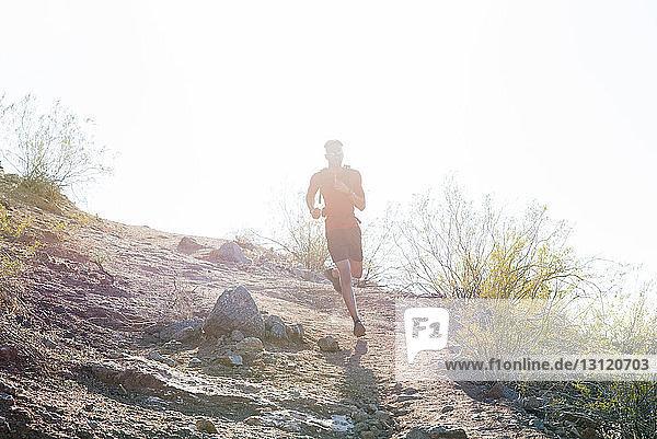 Männlicher Wanderer in voller Länge läuft am sonnigen Tag auf Berg gegen klaren Himmel