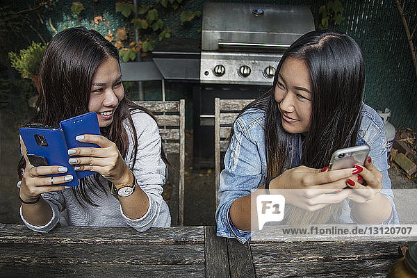 Happy female friend holding smart phone and looking face to face