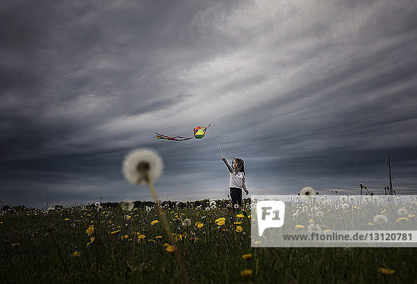 Girl playing with kite while standing on dandelion field against stormy clouds