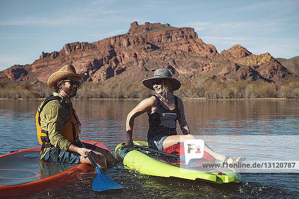 Happy couple sitting on paddleboards at lake