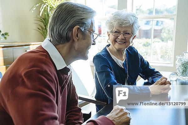 Glückliches älteres Ehepaar sitzt im Büro des Finanzberaters