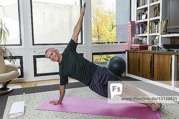 Ein reifer Mann  der zu Hause auf einer Übungsmatte Yoga praktiziert