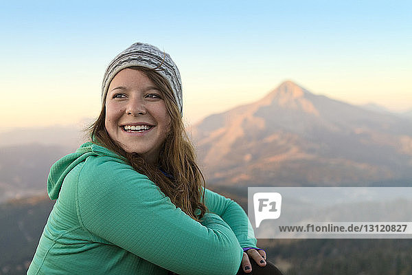 Glückliche Frau schaut weg  während sie auf Berg gegen Himmel sitzt