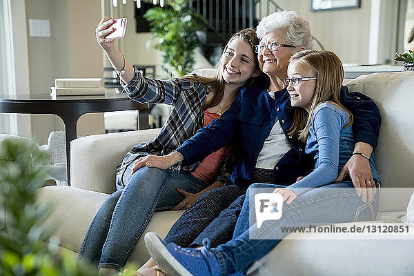 Happy grandmother and granddaughters taking selfie through smart phone while sitting on sofa