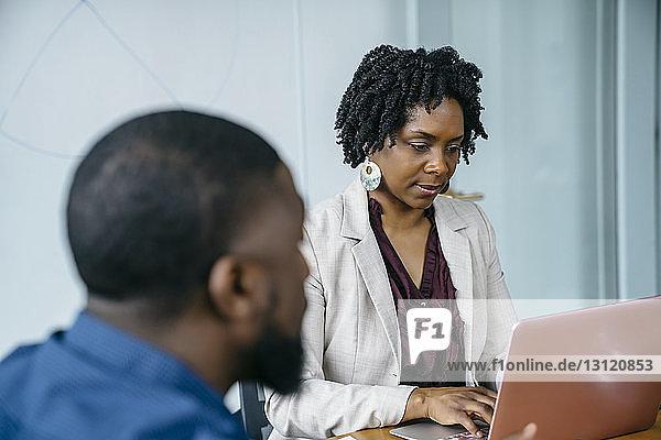 Geschäftsfrau benutzt Laptop-Computer  während sie mit einem Kollegen im Büro sitzt
