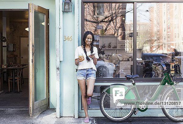 Glückliche Frau benutzt Mobiltelefon  während sie mit dem Fahrrad auf dem Bürgersteig steht