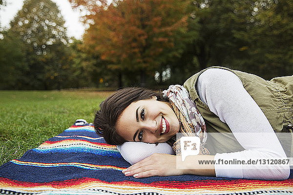 Portrait of happy woman lying on blanket at park