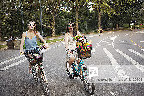 Smiling women cycling on city street against trees