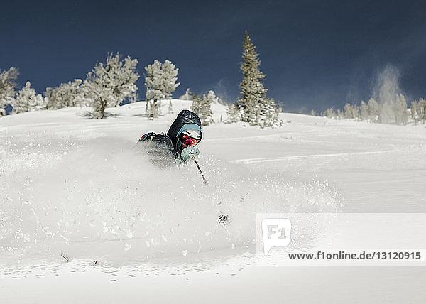 Frau fährt Ski auf schneebedeckter Landschaft gegen den Himmel