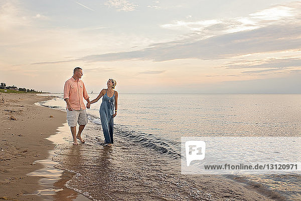 Loving couple holding hands while walking on shore at beach during sunset