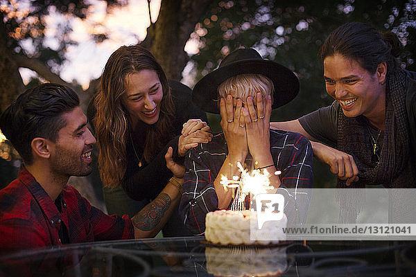 Frau bedeckt ihr Gesicht  während Freunde Geburtstagskuchen anschauen