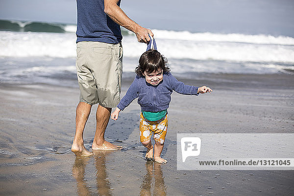 Low section of playful father pulling daughter's jacket while standing on shore at beach