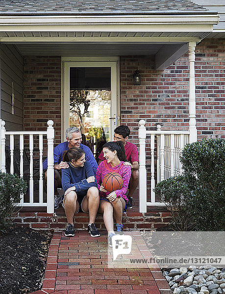 Happy family sitting on front stoop outside house