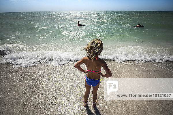 High angle view of girl with hands on hip standing at beach