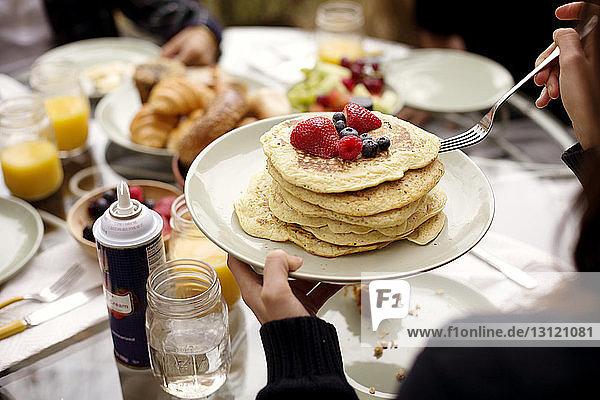 Beschnittenes Bild einer Frau  die Pfannkuchen am Frühstückstisch hält