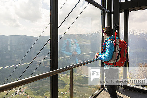 Side view of female hiker looking at view through glass window at observation point