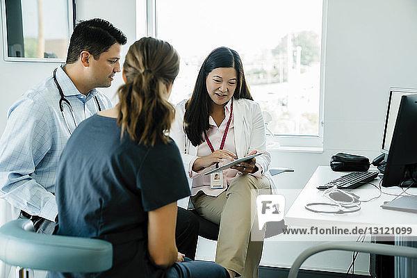 Ärztin zeigt Kollegen im Krankenhaus einen Tablet-PC