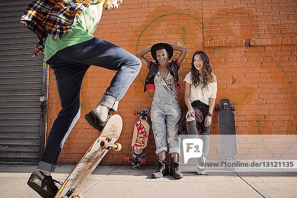 Freundinnen beobachten Mann bei Skateboard-Stunt