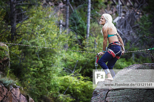 Side view of woman holding rope while standing on rock