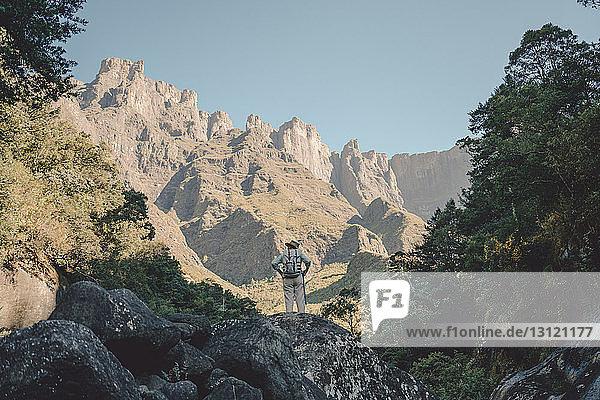 Rückansicht eines Wanderers mit Rucksack beim Wandern auf dem Berg vor klarem Himmel