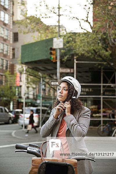 Geschäftsfrau mit Helm  die beim Fahrrad auf der Straße steht