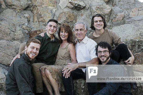 Porträt von glücklichen Söhnen mit Eltern  die im Park vor Felsformationen sitzen