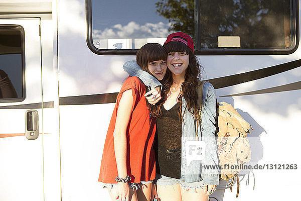 Happy young women on road trip standing together against vanity van