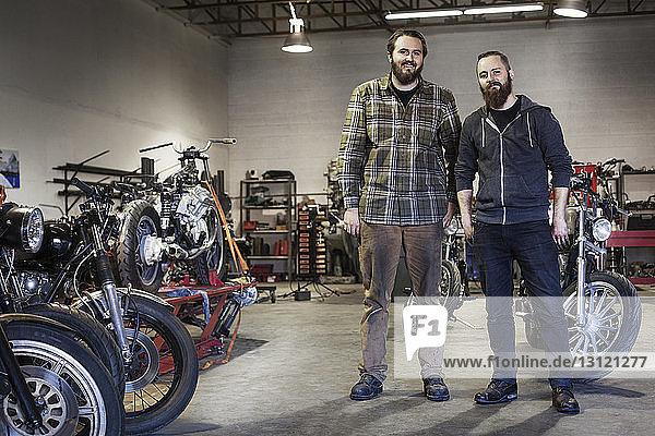 Zuversichtliche Mechaniker stehen bei Motorrädern in der Autowerkstatt