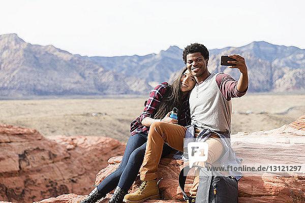 Fröhliche Freunde  die sich mit dem Handy selbstständig machen  während sie auf Felsformationen vor klarem Himmel sitzen