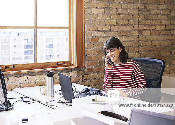 Smiling businesswoman talking on smart phone while sitting at desk in office
