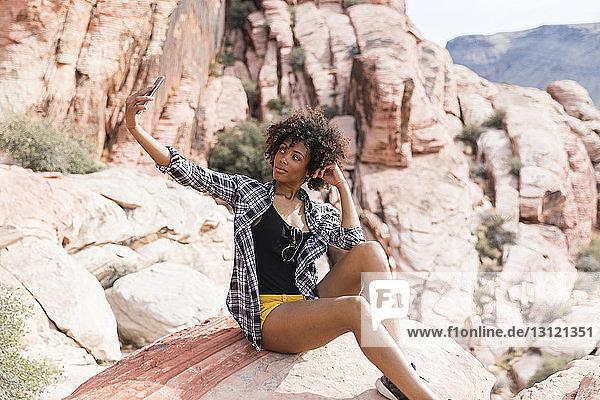 Frau  die bei Sonnenschein auf einer Felsformation sitzend Selbsthilfe nimmt