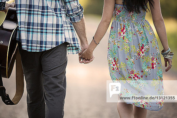 Rückansicht eines Paares  das die Hand hält und auf der Straße geht