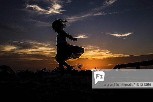 Low angle view of silhouette girl dancing on field against sky during sunset