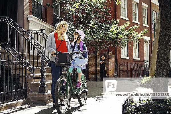 Happy woman talking to daughter sitting on bicycles by building