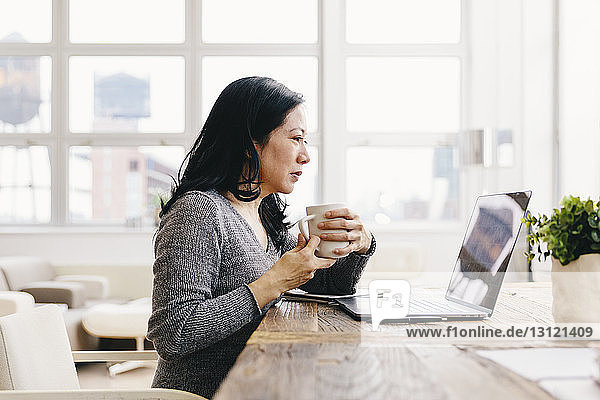 Businesswoman holding coffee cup while looking at laptop computer on desk in office
