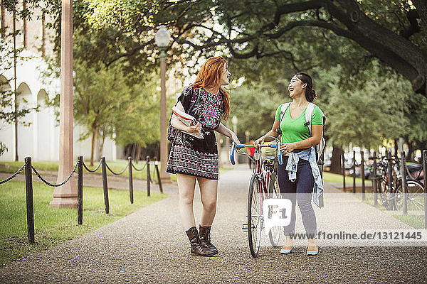 Happy friends walking with bicycle on footpath