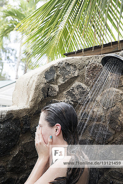 Side view of naked woman bathing under shower