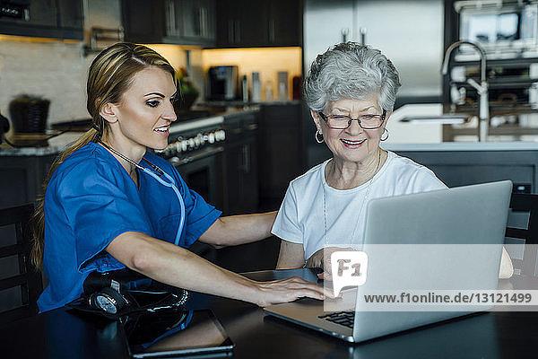 Hauspflegerin und ältere Frau schauen auf Laptop-Computer auf dem Esstisch