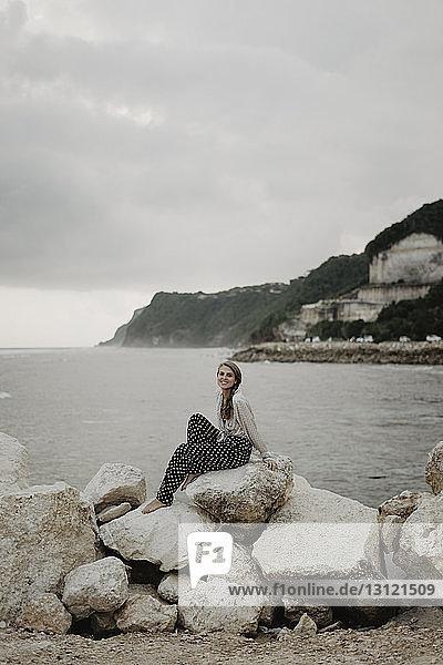 Frau in voller Länge auf Felsen am Strand sitzend