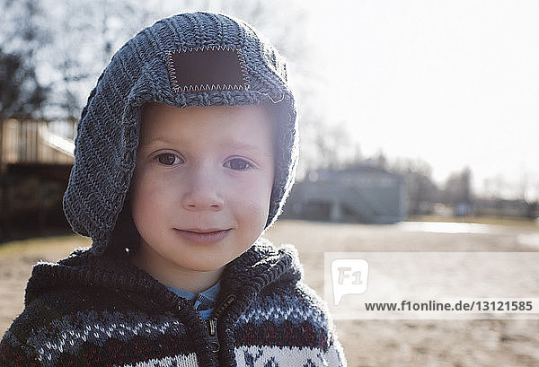 Close-up portrait of boy in warm clothing standing on field against clear sky